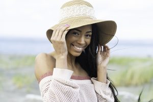 Pretty African American woman wearing floppy hat with a smile at the beach